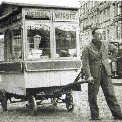 Erster fahrbarer Würstelstand (LEO) mit dessen Gründer Leopold Mlynek sen. (ca 1928)